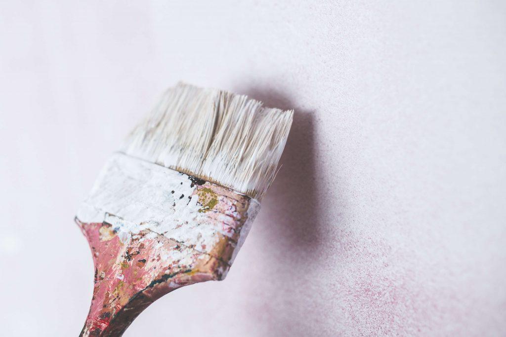 pinceau qui peinture mur blanc